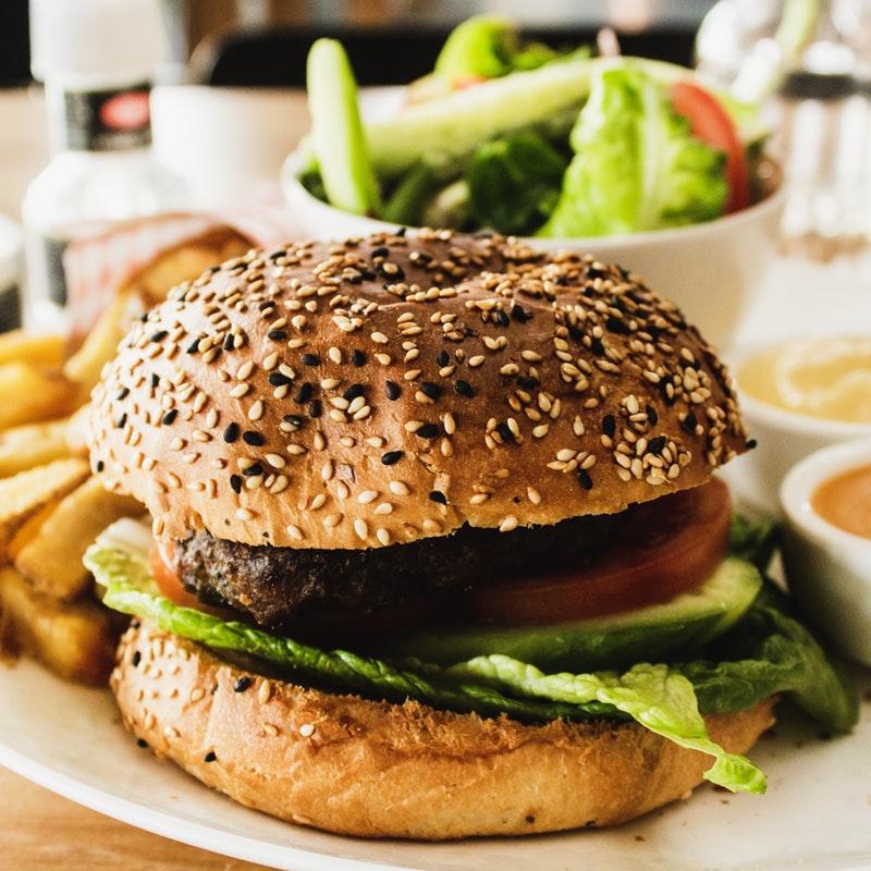 hamburger avec frites et salade dans un pain sésame